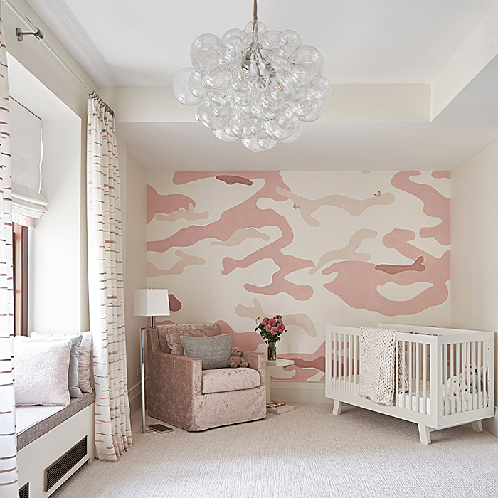 Nursery design with crib, pink chair and light fixture